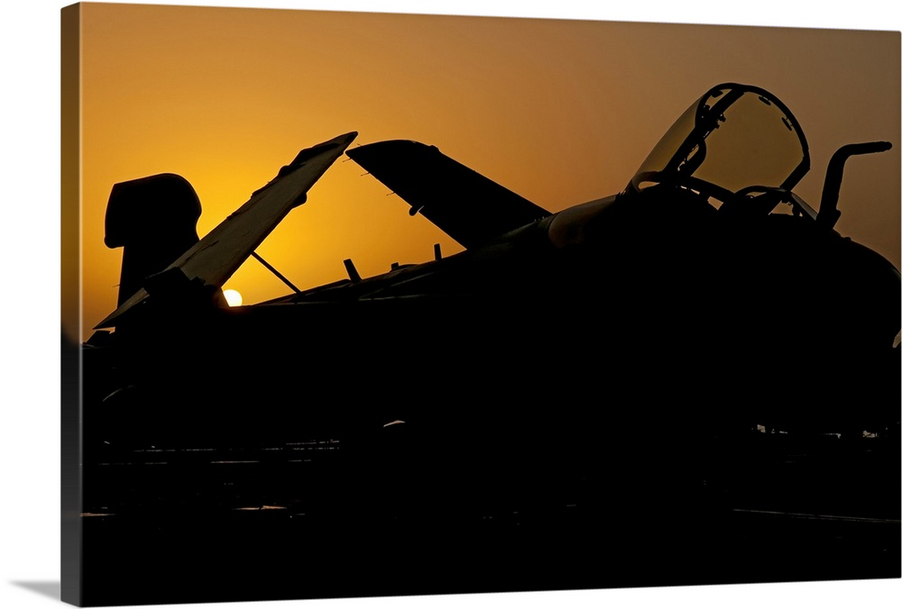 Large Solid-Faced Canvas Print Wall Art Print 36 x 24 entitled Silhouette of an EA-6B Prowler at sunrise on the flight dec... Solid-Faced Canvas Print entitled Silhouette of an EA-6B Prowler at sunrise on the flight deck of USS Nimitz.  Silhouette of an EA-6B Prowler at sunrise on the flight deck of USS Nimitz during Operation Enduring Freedom. Nimitz is operating in the 5th fleet area of responsibility.  Multiple sizes available.  Primary colors within this image include Orange, Brown, Black.  Made in USA.  Satisfaction guaranteed.  Archival-quality UV-resistant inks.  Archival inks prevent fading and preserve as much fine detail as possible with no over-saturation or color shifting.  Canvas depth is 1.25 and includes a finished backing with pre-installed hanging hardware.