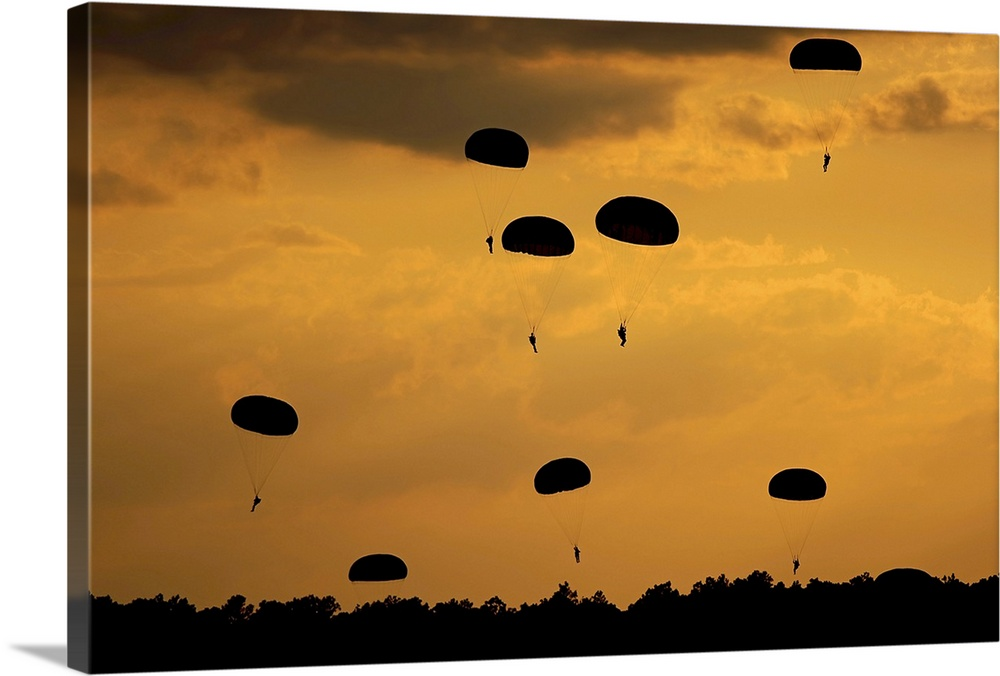 Large Gallery-Wrapped Canvas Wall Art Print 24 x 16 entitled U.S. Army Soldiers parachute through the sky Gallery-Wrapped Canvas entitled U.S. Army Soldiers parachute through the sky.  Landscape large photograph taken on September 12 2010 of a group of U.S. Army Soldiers from the 82nd Airborne Division parachuting down on to drop zone Luzon after jumping from a C-130 Hercules during Airborne Operations at Fort Bragg North Carolina.  Multiple sizes available.  Primary colors within this image include Brown Peach Black.  Made in the USA.  Satisfaction guaranteed.  Archival-quality UV-resistant inks.  Canvas is designed to prevent fading.  Canvas is acid-free and 20 millimeters thick.