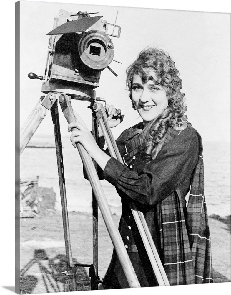 Large Solid-Faced Canvas Print Wall Art Print 24 x 30 entitled Mary Pickford (1893-1979) Solid-Faced Canvas Print entitled Mary Pickford 1893-1979.  Born Gladys Mary Smith. American actress, with a movie camera on a beach, c1916.  Multiple sizes available.  Primary colors within this image include Dark Gray, White.  Made in the USA.  Satisfaction guaranteed.  Inks used are latex-based and designed to last.  Canvas is handcrafted and made-to-order in the United States using high quality artist-grade canvas.  Featuring a proprietary design, our canvases produce the tightest corners without any bubbles, ripples, or bumps and will not warp or sag over time.