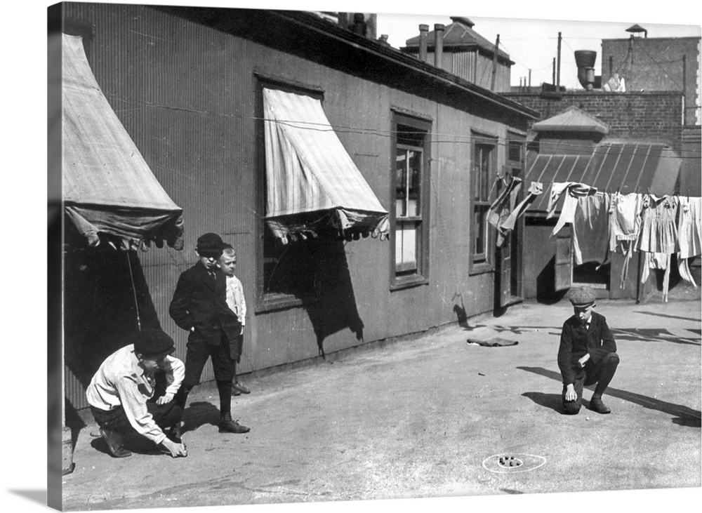 Large Gallery-Wrapped Canvas Wall Art Print 24 x 17 entitled New York City: Marble Game Gallery-Wrapped Canvas entitled New York City Marble Game.  Children playing a game of marbles on a rooftop in New York City. Photograph, c1910.  Multiple sizes available.  Primary colors within this image include Dark Gray, Silver.  Made in USA.  All products come with a 365 day workmanship guarantee.  Inks used are latex-based and designed to last.  Canvas frames are built with farmed or reclaimed domestic pine or poplar wood.  Canvases are stretched across a 1.5 inch thick wooden frame with easy-to-mount hanging hardware.