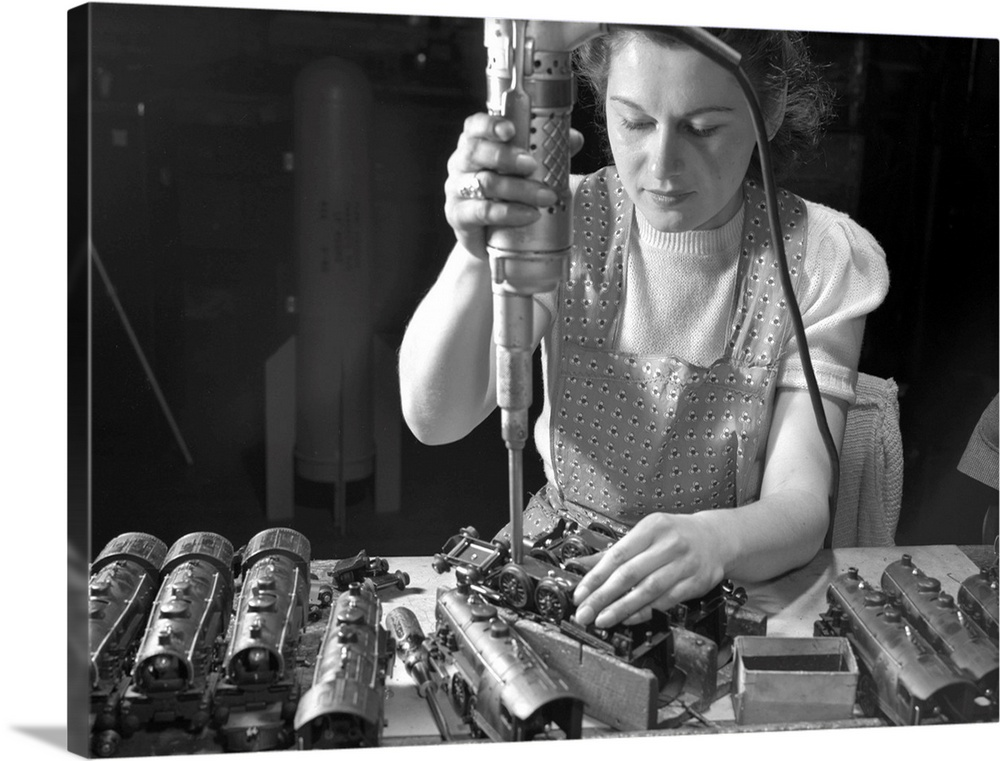 Large Gallery-Wrapped Canvas Wall Art Print 24 x 18 entitled Toy Factory, 1942 Gallery-Wrapped Canvas entitled Toy Factory 1942.  Worker Stephanie Cewe using an electric screwdriver to assemble locomotives for toy trains at a factory in New Haven Connecticutshortly before the plant was converted to the manufacture of parachute flare casings during World War II. Photographed by Howard R. Hollem 1942.  Multiple sizes available.  Primary colors within this image include Dark Gray Light Gray.  Made in the USA.  All products come with a 365 day workmanship guarantee.  Archival-quality UV-resistant inks.  Canvases have a UVB protection built in to protect against fading and moisture and are designed to last for over 100 years.  Canvas is a 65 polyester 35 cotton base with two acrylic latex primer basecoats and a semi-gloss inkjet receptive topcoat.