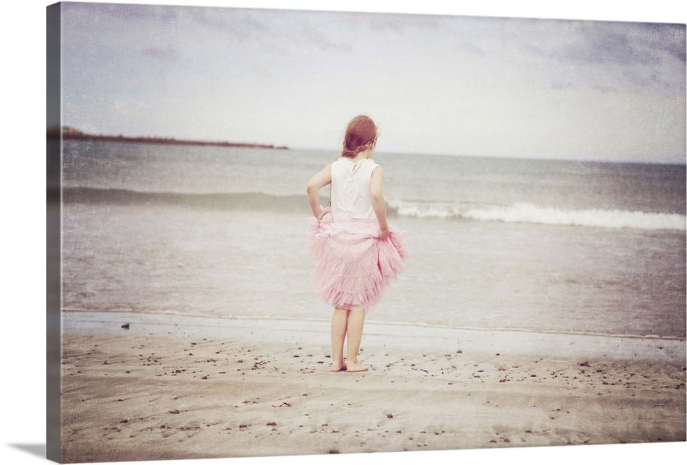 Large Gallery-Wrapped Canvas Wall Art Print 24 x 16 entitled Girl in tulle at beach edge Gallery-Wrapped Canvas entitled Girl in tulle at beach edge.  A young girl dressed in a pink sleeveless top and pink layered tulle skirt stands holding her skirt up at the waters edge of a beach.  A pale blue sky grey and white clouds gently rolling waves.  A textured photo.  Multiple sizes available.  Primary colors within this image include Pink Black Gray Silver.  Made in USA.  Satisfaction guaranteed.  Archival-quality UV-resistant inks.  Canvas frames are built with farmed or reclaimed domestic pine or poplar wood.  Canvases are stretched across a 1.5 inch thick wooden frame with easy-to-mount hanging hardware.