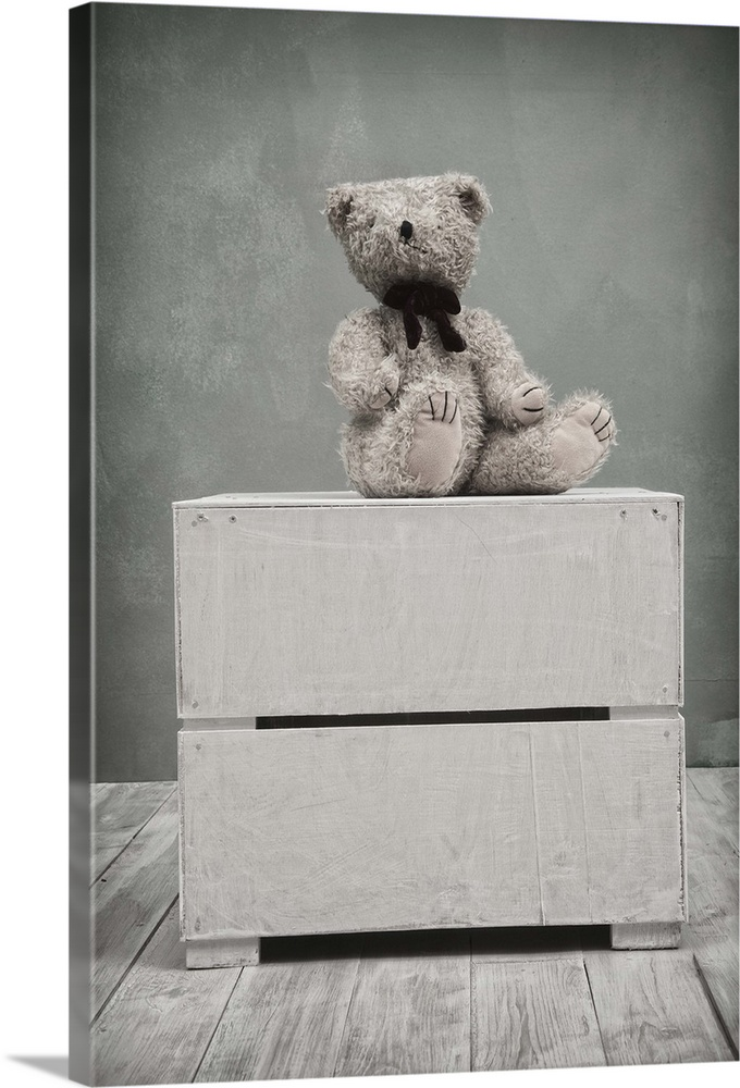 Large Solid-Faced Canvas Print Wall Art Print 20 x 30 entitled My Bear Solid-Faced Canvas Print entitled My Bear.  Small toy bear sat on the top of a box in a childrens playroom.  Multiple sizes available.  Primary colors within this image include Dark Gray, Silver.  Made in USA.  Satisfaction guaranteed.  Inks used are latex-based and designed to last.  Archival inks prevent fading and preserve as much fine detail as possible with no over-saturation or color shifting.  Canvas is handcrafted and made-to-order in the United States using high quality artist-grade canvas.
