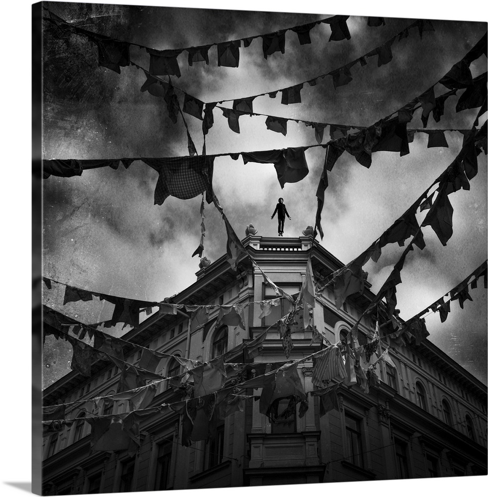 Large Gallery-Wrapped Canvas Wall Art Print 16 x 16 entitled Night Flight Gallery-Wrapped Canvas entitled Night Flight.  Conceptual image of young adult male falling from tall building with clothes hung from bunting across street.  Multiple sizes available.  Primary colors within this image include Black, Light Gray.  Made in the USA.  Satisfaction guaranteed.  Archival-quality UV-resistant inks.  Canvases have a UVB protection built in to protect against fading and moisture and are designed to last for over 100 years.  Canvas is designed to prevent fading.